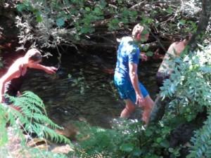 Deelnemers banen zich een weg door de rivier tijdens de River Hike