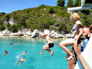 Zeb springt van de boot in een baai van Paxos