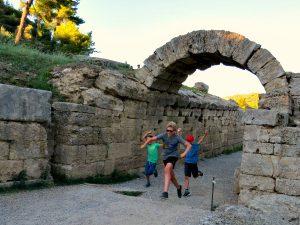De jongens rennen onder de triomfboog in het oude Olympia