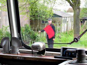 De conducteur zwaait met zijn vlag bij een spoorwegovergang