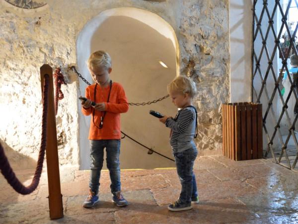 De kinderen luisteren naar de Audiotour in burcht Hohenwerfen