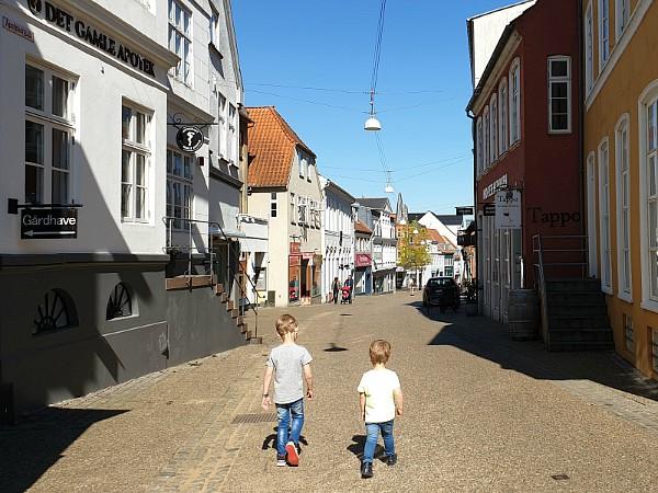 De kids wandelen door het oude straatjes van Haderslev