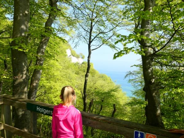 Sanne kijkt door het bos naar de zee