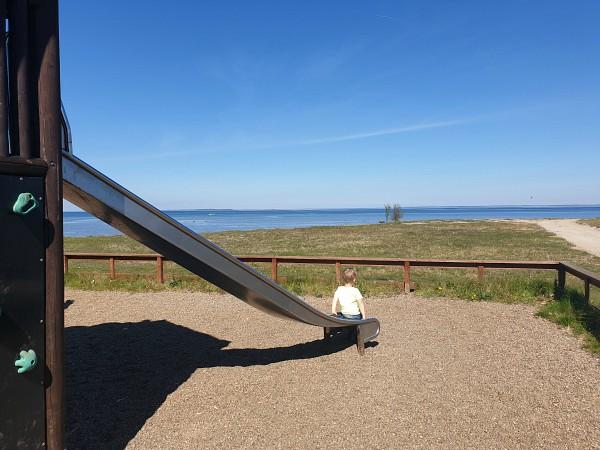 peuter glijdt van de glijbaan met uitzicht op zee.