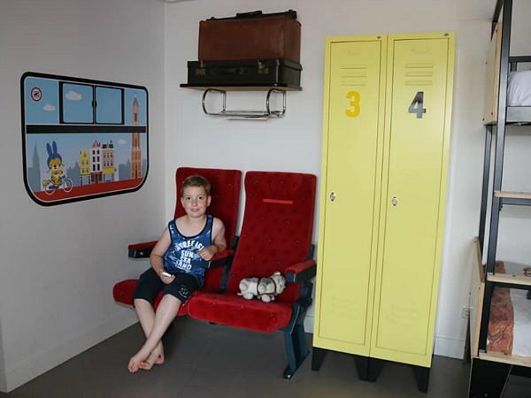 Een leuke zithoek met vintage treinstoelen, bagagerek met koffers en lockerkast.
