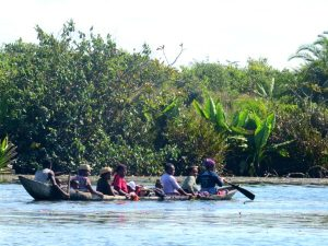 Een familie vervoert zich per kano over het Pangalanes kanaal